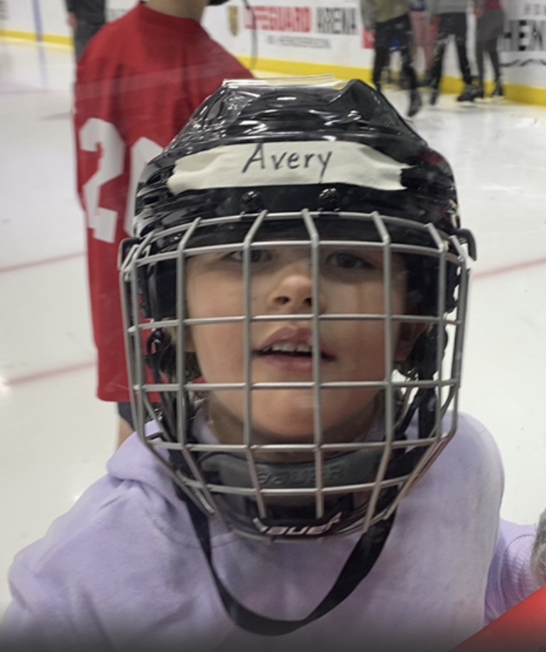 Photo of a youth smiling while wearing a hockey helmet
